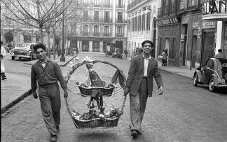 Cargando una cesta de Navidad cuesta arriba en Calle Infantas el 19 de diciembre de 1950