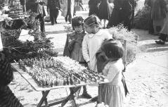 Unas niñas miran las figuritas navideñas en los puestos de Tirso de Molina, fotografiados por Pepe Campúa el 19 de diciembre de 1950