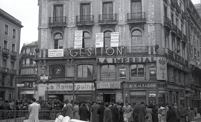 Los periodistas y la gente se arremolinaba en torno al edificio de Doña Manolita en para ir viendo los números premiados. Foto de Campúa tomada el 22 de diciembre de 1950