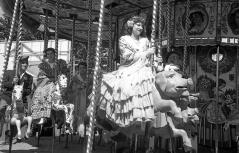 Mujeres engalanadas con claveles montan en el tiovivo en la Verbena de San Antonio en 1952.