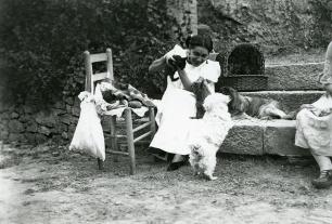 Raquel Meller jugando con unos cachorritos en sus vacaciones en 1921